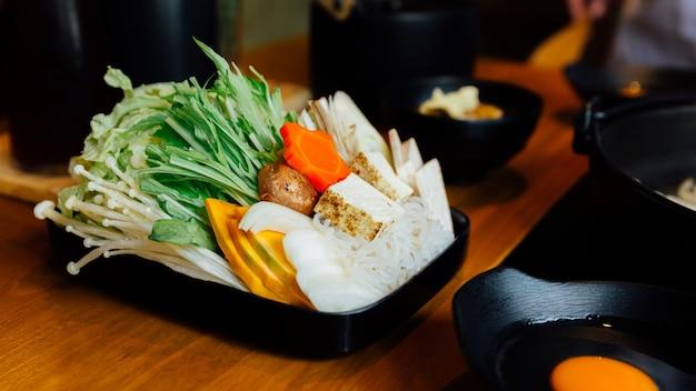 Verdure di sukiyaki messe in piatto nero.