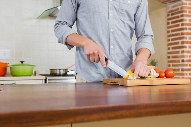 Verdure di taglio del giovane sul tagliere in cucina