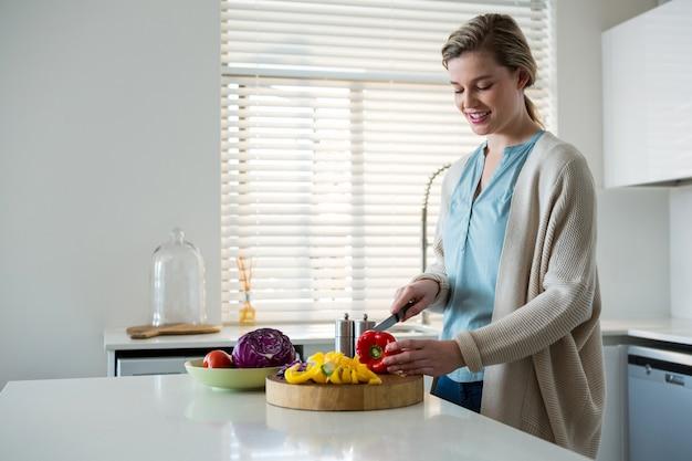 Verdure di taglio della donna in cucina