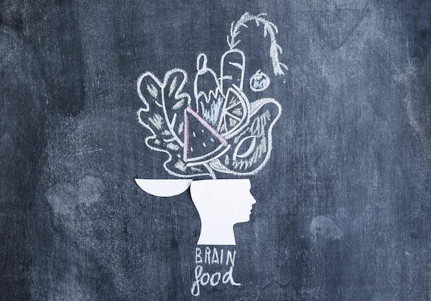 Verdure disegnate sopra la testa aperta sulla lavagna