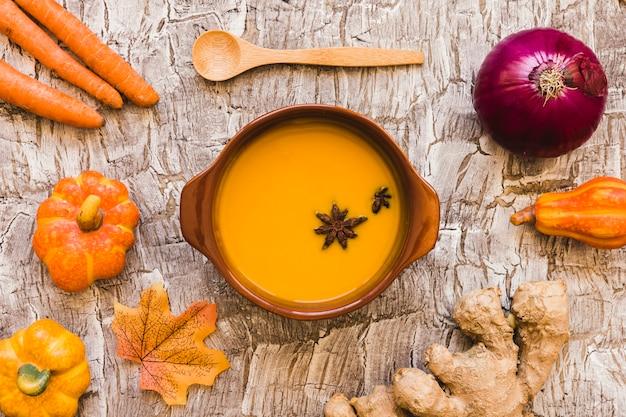 Verdure e foglie intorno zuppa e cucchiaio