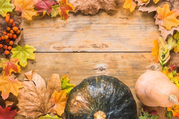 Verdure e foglie secche su tavola di legno