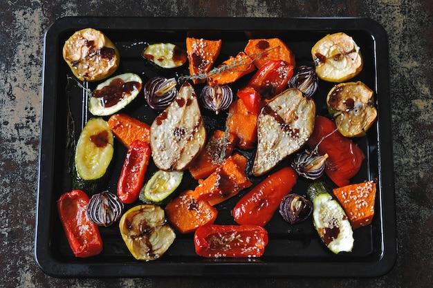 Verdure e frutta cotte su una teglia. tema vegan. appetitosi verdure al forno e frutta con spezie.