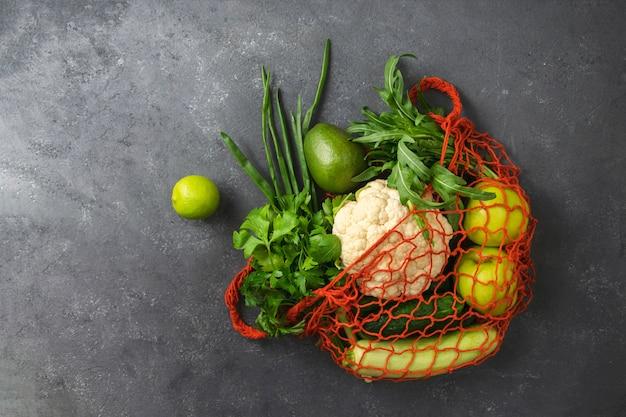 Verdure e frutta organiche in una borsa di drogheria sul nero