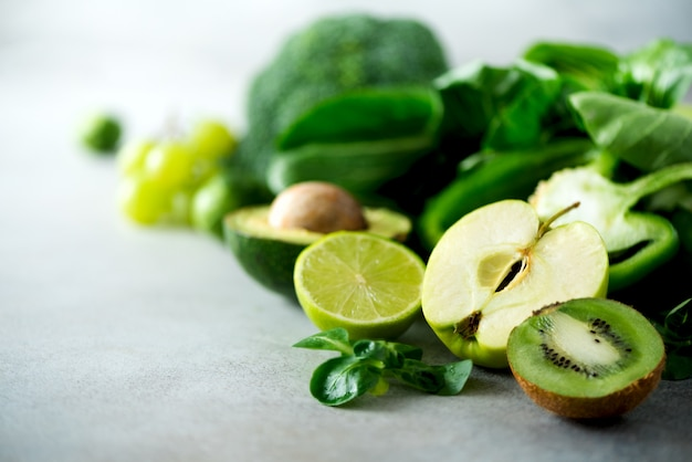Verdure e frutta verdi organiche su fondo grigio. mela verde, lattuga, cetriolo, avocado, cavolo, lime, kiwi, uva, banana, broccoli