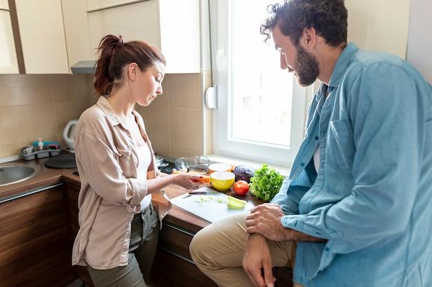 Verdure e marito di taglio della moglie che si siedono sul contatore