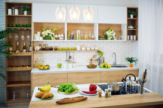 Verdure e pane disposti sulla tavola di legno.