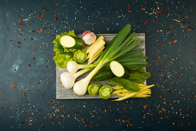 Verdure e spezie fresche su una scheda di legno su una pietra scura. il concetto di vintage. spezia il giovane cucumber di pomodoro verde di asparagi su una superficie scura.