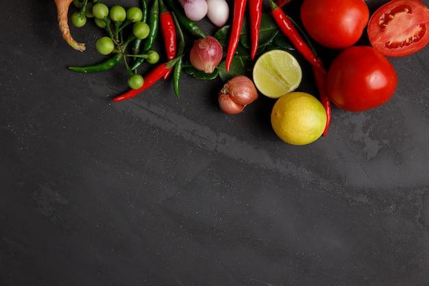 Verdure e spezie per cucinare su sfondo scuro