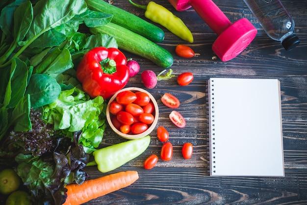 Verdure e taccuino organici freschi con il dumbbell su legno nero