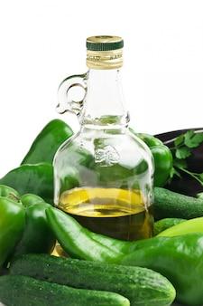 Verdure e una bottiglia di olio, natura morta isolata su bianco