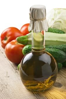 Verdure e una bottiglia di olio, natura morta su un tavolo di legno