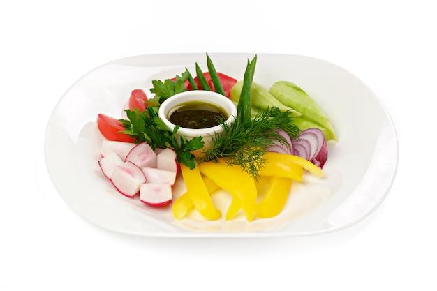 Verdure fresche a fette con salsa nel piatto su bianco