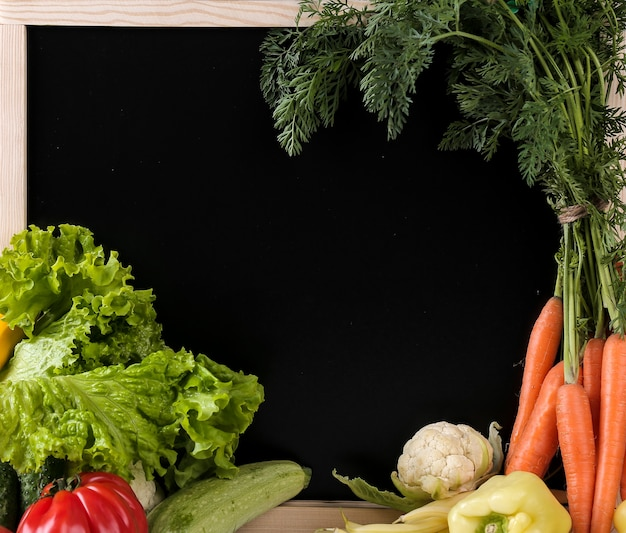 Verdure fresche con una lavagna