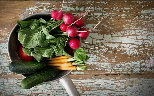 Verdure fresche dell'azienda agricola in ciotola. ravanello, carota, cetriolo e pomodoro sul vecchio bordo rustico in legno vista dall'alto,
