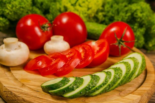 Verdure fresche. pomodori, cetrioli e funghi su una tavola di legno. delizioso cibo vegetariano. insalata.