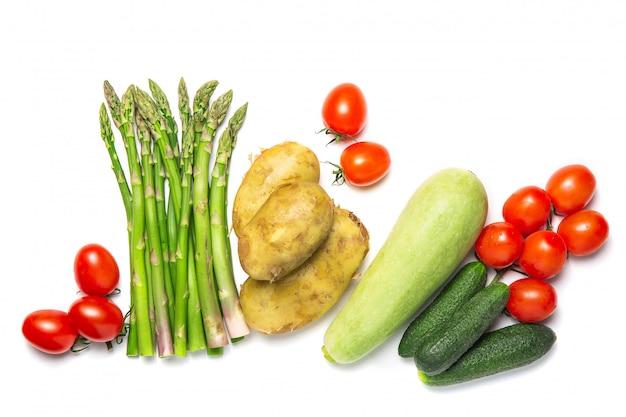 Verdure fresche su uno sfondo bianco isolato. colture. asparagi, pomodori, zucchine. disteso.