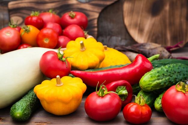 Verdure fresche - zucca, cetrioli, pomodori, zucchine, peperoni su un tavolo di legno
