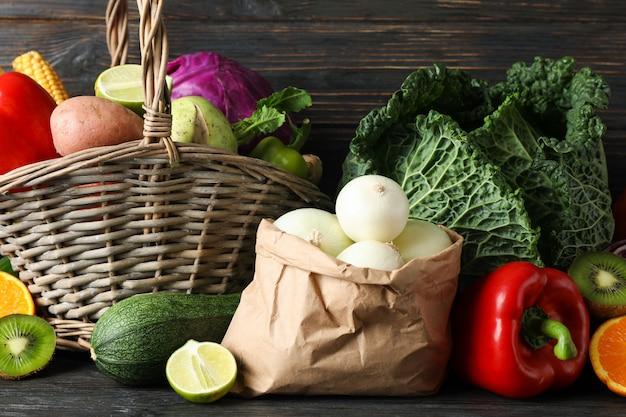 Verdure, frutta, cestino di vimini e sacco di carta su legno