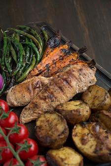 Verdure grigliate su un tagliere su un fondo di legno scuro. sfondo di legno scuro