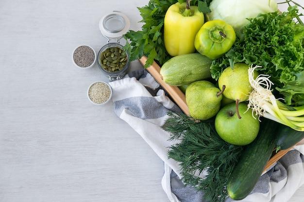 Verdure ipoallergeniche verdi in scatola di legno e semi. cibo vegetariano. messa a fuoco selettiva, vista dall'alto