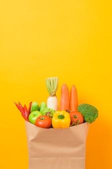 Verdure nel sacchetto di drogheria sulla parete gialla