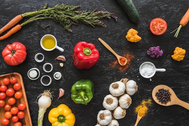 Verdure; olio e spezie sul bancone da cucina nero grezzo