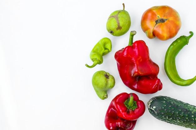 Verdure organiche brutte d'avanguardia: pere, cetriolo, peperoni, peperoncino e pomodoro su fondo bianco