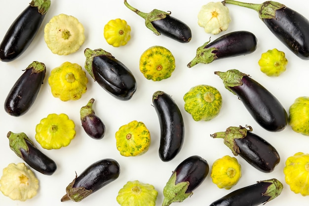 Verdure organiche del modello: patissons e melanzana su fondo bianco, concetto dell'alimento biologico, orientamento orizzontale