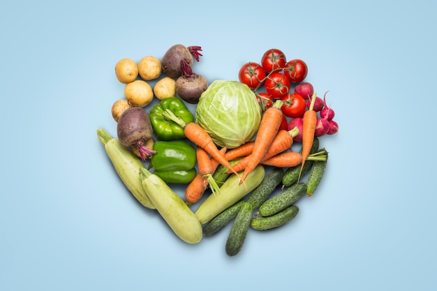 Verdure organiche fresche su una superficie blu. concetto di acquisto di ortaggi agricoli, cura della salute, raccolta. a forma di cuore. stile country, fiera agricola. vista piana, vista dall'alto