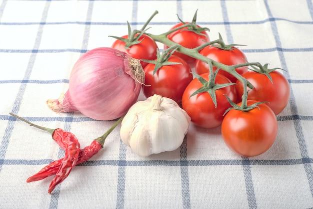 Verdure, pepe, aglio, cipolla, pomodori su tela quadrata