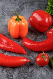 Verdure rosse e gialle sulla tavola grigia.
