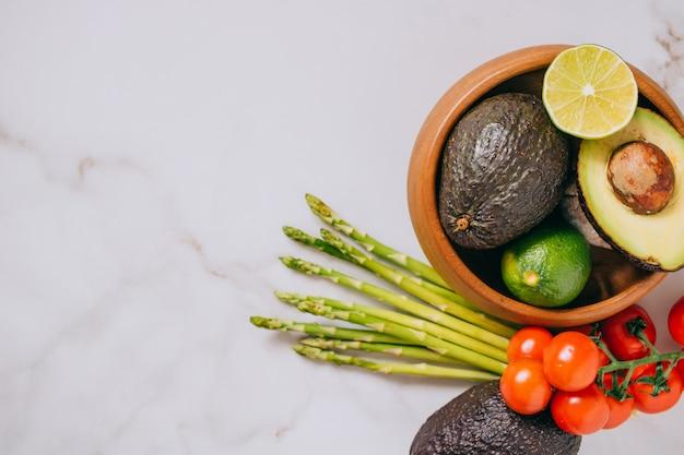 Verdure sane fresche in piatto di legno su fondo di marmo bianco