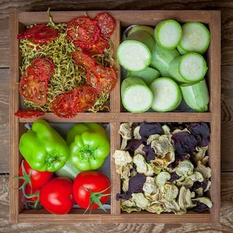 Verdure secche del primo piano di vista superiore e ortaggi freschi in scatola di legno
