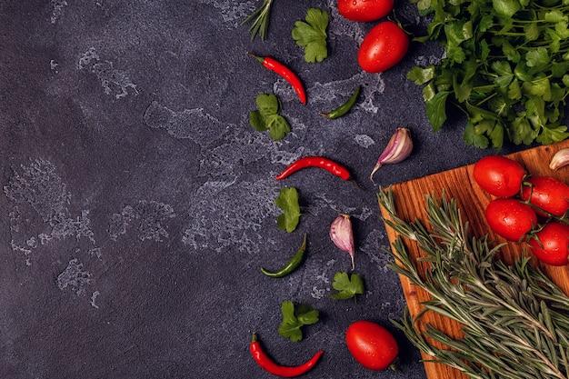 Verdure, spezie, erbe per cucinare - prezzemolo, rosmarino, pomodoro, aglio, peperoncino