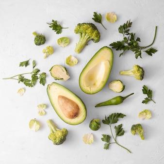 Verdure su fondo bianco con l'avocado sul centro