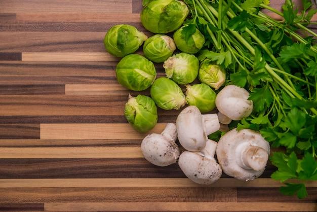 Verdure su legno. bio cibo sano, erbe e spezie. verdure organiche su legno. pagina con verdure organiche verdi su sfondo di legno con spazio di copia