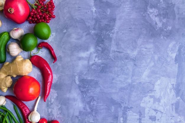 Verdure variopinte di frutta e verdura colorate antiossidanti organiche fresche estive gustose: avocado, pomodoro, aglio, peperoncino, zenzero isolato su sfondo grigio. concetto di cibo sano vegano e vegetariano