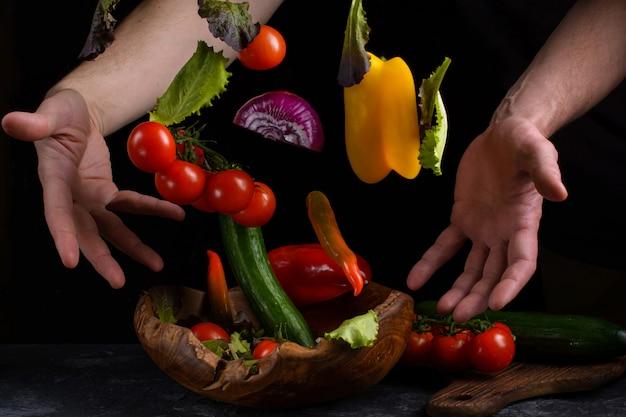 Verdure volanti per insalata tra mani maschili. il cibo vegetariano sano è la levitazione
