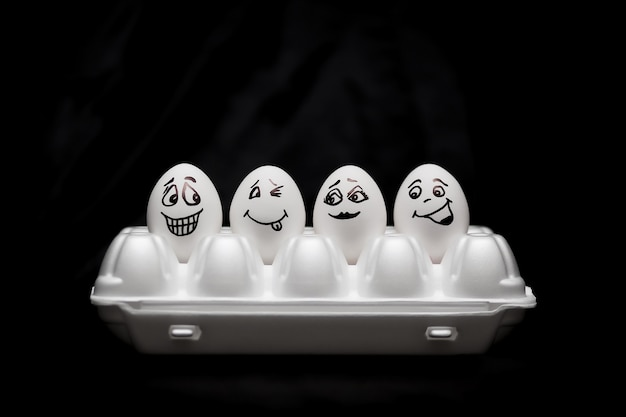 Vere uova dipinte a mano. uova bianche con facce disegnate disposte in cartone.