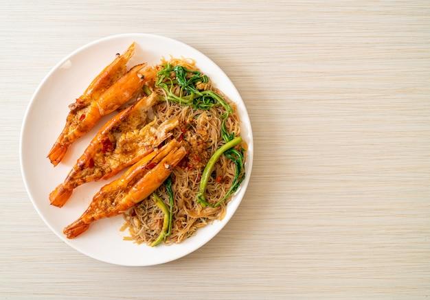 Vermicelli di riso in padella e mimosa d'acqua con gamberi di fiume sul piatto