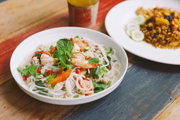 Vermicelli di riso piccante con gamberetti, carne di maiale macinata e peperoncino. guarnire con foglie di menta.