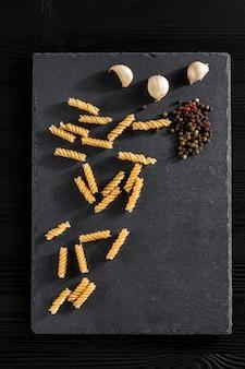 Vermicelli garlick finocchio pepe di basilico su una pietra nera