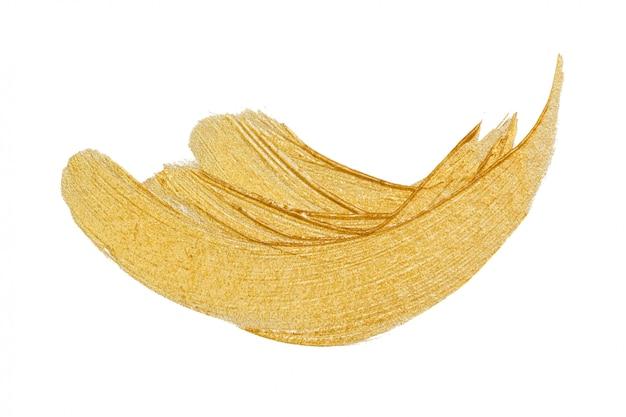 Vernice dell'oro o colpi metallici di trucco isolati su bianco