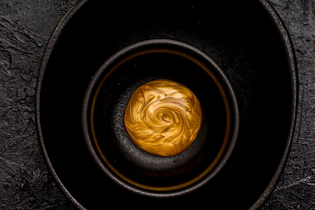 Vernice dorata sciolta in una ciotola nera