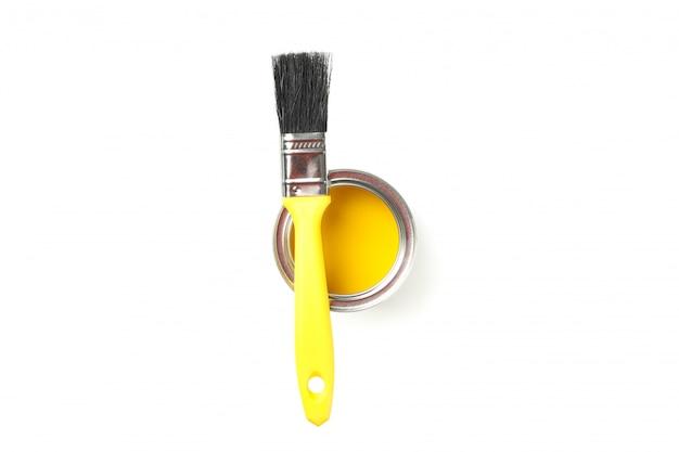Vernice gialla e pennello isolati su superficie bianca