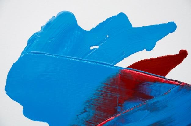 Vernice rossa e blu su sfondo bianco