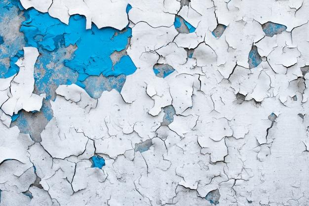 Vernice scrostata su un muro di cemento. fondo astratto dipinto blu e bianco, superficie incrinata di lerciume, struttura del modello.