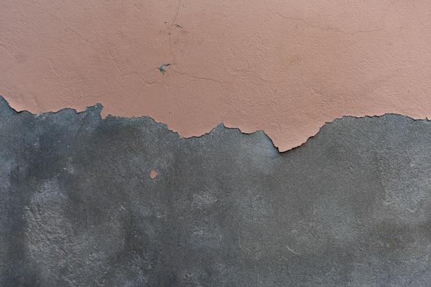 Vernice scrostata sullo sfondo di consistenza granulosa muro di cemento