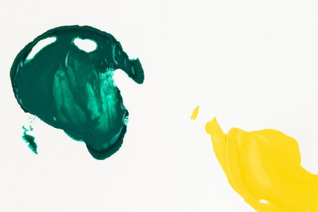 Vernice verde e gialla spalmata su sfondo bianco
